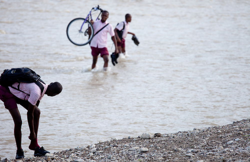 Schoolkids cross a river on their way to school near Port Salut on the Tiburon Peninsula of Haiti
