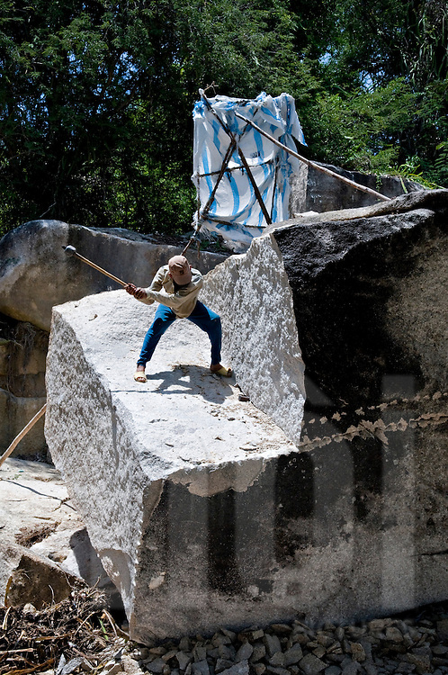 A man stands on a huge rock and tries to slice the mineral with a sledgehammer and a wedge. Khanh Hoa area, Vietnam, Asia