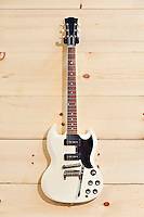 White guitar on wood grain wall