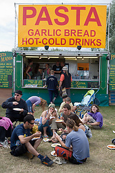 People sitting on the grass eating pasta at an cafe at the WOMAD (World of Music; Arts and Dance) Festival in reading; 2005,