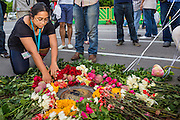 """24 JUNE 2014 - BANGKOK, THAILAND: Members of the """"Monsoon Poets Society"""" lay roses at the spot where the """"People's Party"""" demanded a constitutional monarchy during a bloodless coup in 1932. The poets  gathered in front of the Anantasamakom Throne Hall Tuesday to pay homage to the People's Party, a Siamese (Thai) group of military and civil officers (which became a political party) that staged a bloodless coup against King Prajadhipok (Rama VII) and changed Thailand (then Siam) from an absolute monarchy to a constitutional monarchy on 24 June 1932. Since the coup against the civilian government on 22 May, the ruling junta has not allowed political gatherings. Although police read the poems, they did not arrest any of the poets or make any effort to break up the gathering.     PHOTO BY JACK KURTZ"""