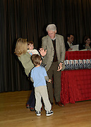 President Bill Clinton offers young boy a high five at signing of his new book Back to Work at his hometown library in Chappaqua, New York. Approximately  500 people attended the book signing on Friday, December 9, 2011. The Village Bookstore in neighboring  Pleasantville, New York, which sponsored the event,  donated 10% of their profits from the sale to the library as a way of saying thank you for providing the venue for the event.