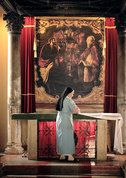A Roman Catholic nun in grey habit and black veil draws a clean white altar cloth over the stone altar in the church of Sveti Mihovil in Korcula, Croatia.  The altarpiece is a mannerist painting by Domenico Maggiotto, 18th century, of the Trinity with two saints, one wearing a halo.  The nun concentrates on her task, which, even though a simple daily one, seems part of her spirituality.  No doubt she whispers a prayer as the cloth slides over the stone.
