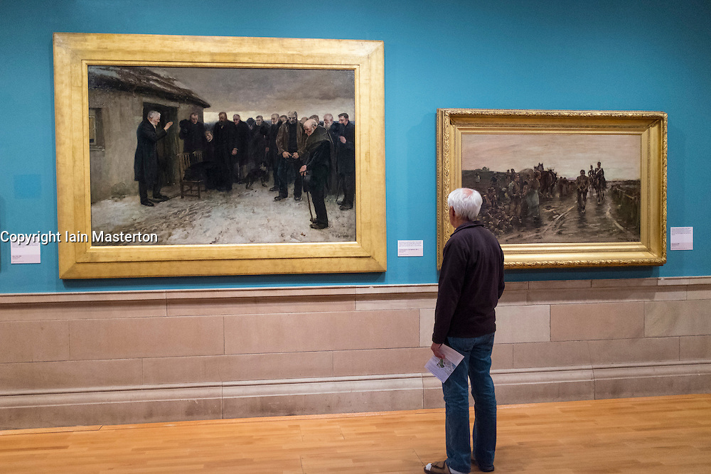 Visitor looking at painting A Funeral Service in the Highlands by James Guthrie on display at Kelvingrove Art Gallery and Museum in Glasgow United Kingdom