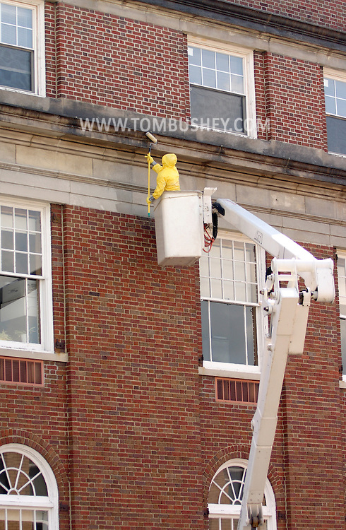 Middletown, N.Y. - A worker in a bucket truck cleans the stonework above the second-floor windows at Middletown City Hall on May 13, 2006. ©Tom Bushey