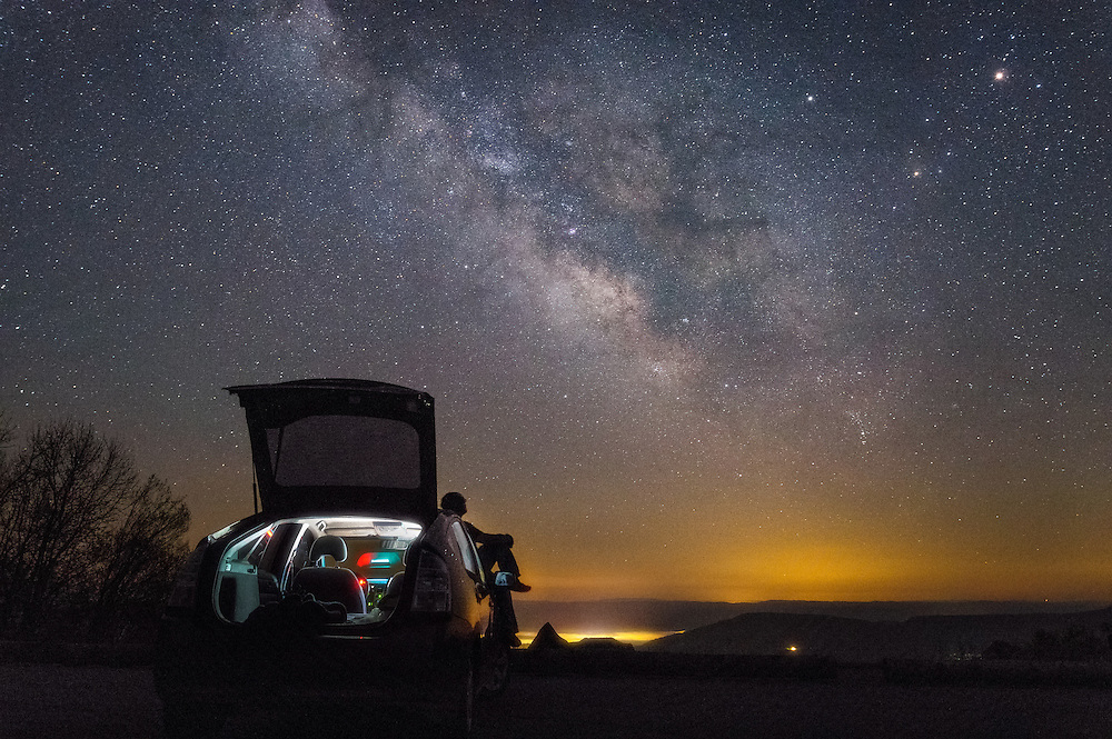 The southern core of the Milky Way above the highlands of West Virginia from an overlook of the small communities of Woodrow and West Union, a lone star gazer rests on the hood of a car, glancing up at the night sky.