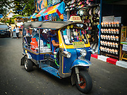 24 NOVEMBER 2015 - BANGKOK, THAILAND: Tuk tuk or three wheeled taxi drives through the Wat Saket temple fair. Wat Saket is on a man-made hill in the historic section of Bangkok. The temple has golden spire that is 260 feet high which was the highest point in Bangkok for more than 100 years. The temple construction began in the 1800s in the reign of King Rama III and was completed in the reign of King Rama IV. The annual temple fair is held on the 12th lunar month, for nine days around the November full moon. During the fair a red cloth (reminiscent of a monk's robe) is placed around the Golden Mount while the temple grounds hosts Thai traditional theatre, food stalls and traditional shows.       PHOTO BY JACK KURTZ