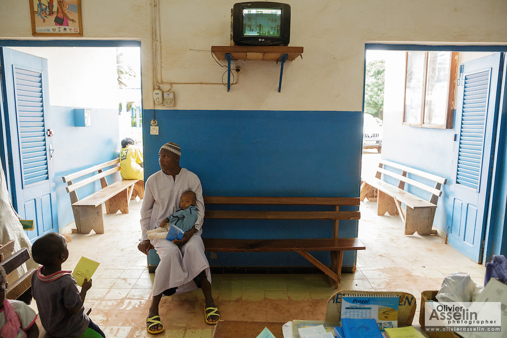 Diallo Amadou, 25, holds his son Diallo Mamadou Kalidou, 9 months, who suffers from anemia and malaria, as they wait at the Libreville health center in Man, Cote d'Ivoire on Wednesday July 24, 2013.