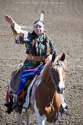 Indian Tribeswoman in traditional dress riding horseback saluting, Ellensburg Rodeo opening ceremony, 2012 WA USA
