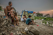 "Men linger is the most impoverished part of Market 3 slum, a space known for both drug use and drug dealing.  The young men in the center of the frame are of the prime age to become victims of extrajudicial killings in Duterte's ""War on Drugs"".  Navotas, Metro Manila, Philippines"