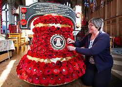 © Licensed to London News Pictures. 9/10/2018. Warwick, UK. Poppy display. Sixty two thousand, four hundred and thirty eight poppies have been assembled in St Mary's  church Warwick to commemorate the ending of the first World War. The poppies have been produced by local people, groups and school children with six hundred and ten alone covering the bell near the altar. As well as red poppies there are differing colours to signify conscious objectors, animals and pigeons killed in the Great War. Pictured, bell ringer Karen French who came up with the idea to decorate the bell adds the finishing touches. Photo credit: Dave Warren/LNP