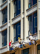 "15 FEBRUARY 2019 - SIHANOUKVILLE, CAMBODIA: Cambodian workers paint the exterior of a new Chinese apartment building in Sihanoukville. There are about 80 Chinese casinos and resort hotels open in Sihanoukville and dozens more under construction. The casinos are changing the city, once a sleepy port on Southeast Asia's ""backpacker trail"" into a booming city. The change is coming with a cost though. Many Cambodian residents of Sihanoukville  have lost their homes to make way for the casinos and the jobs are going to Chinese workers, brought in to build casinos and work in the casinos.      PHOTO BY JACK KURTZ"