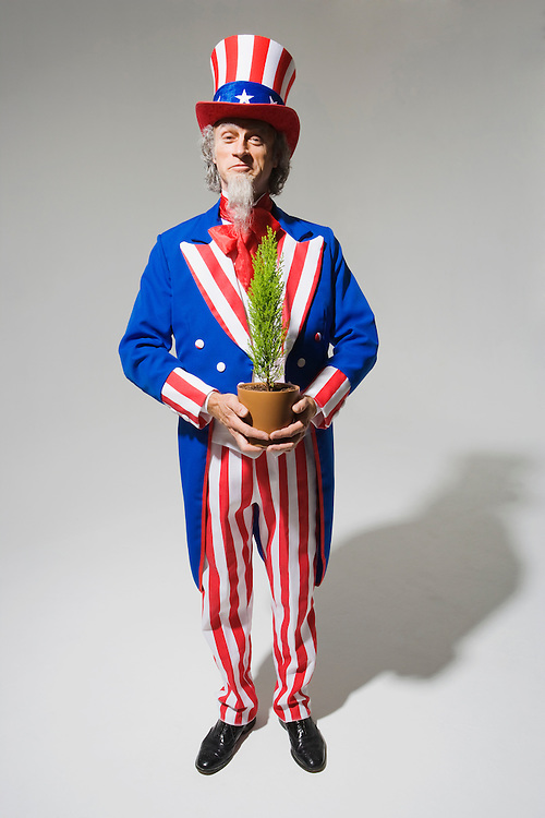 """Uncle Sam holding a small green plant in a pot.  Uncle Sam going """"Green""""...Model Release: 20080626_MR_A"""