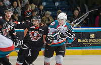 KELOWNA, CANADA, JANUARY 1: Brady Brassart #27 of the Calgary Hitmen is checked by Zach Franko #9 of the Kelowna Rockets as the Calgary Hitmen visit the Kelowna Rockets on January 1, 2012 at Prospera Place in Kelowna, British Columbia, Canada (Photo by Marissa Baecker/Getty Images) *** Local Caption ***