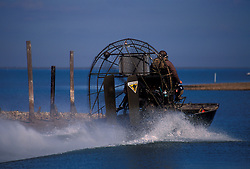 Stock photo of a man operating an air boat on the water