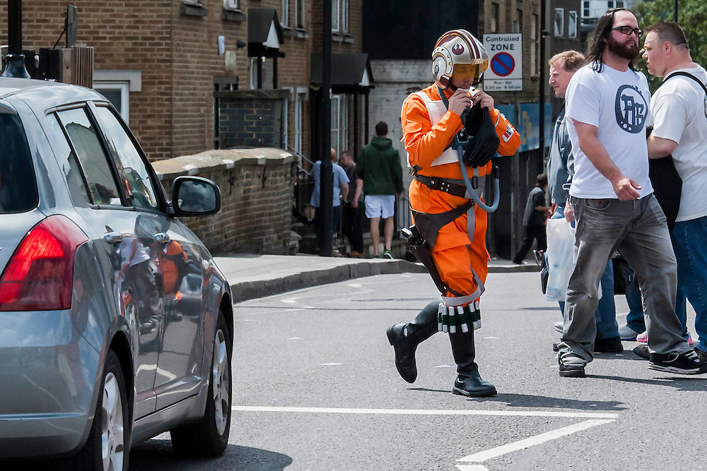 A resistance star fighter from Star Wars crosses the Brompton Road on his way in. London Film and Comic Con 2014, (LFCC), at Earls Court, London, UK.