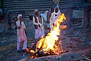 Body burning on funeral pyre at Hindu cremation at Manikarnika crematorium Ghat in Holy City of Varanasi, Benares, India
