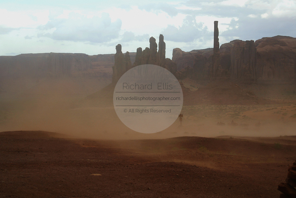 View of the totem pole during a sandstorm in Monument Valley on the southern border of Utah with northern Arizona. The valley lies within the range of the Navajo Nation Reservation. The Navajo name for the valley is Tsé Bii' Ndzisgaii - Valley of the Rocks.