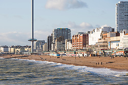 © Licensed to London News Pictures. 25/11/2017. Brighton, UK. Brighton and Hove beach and the Palace Pier basks in sunshine as members of the  public dress up in hats and scarfs. Photo credit: Hugo Michiels/LNP