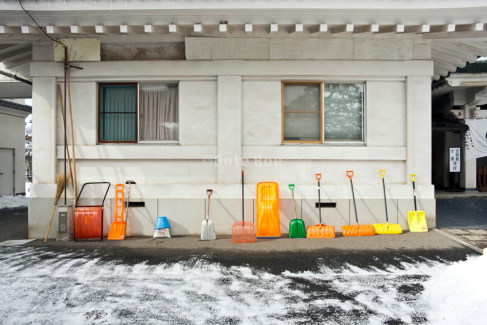 various snow clearing shovels and scoops placed against wall