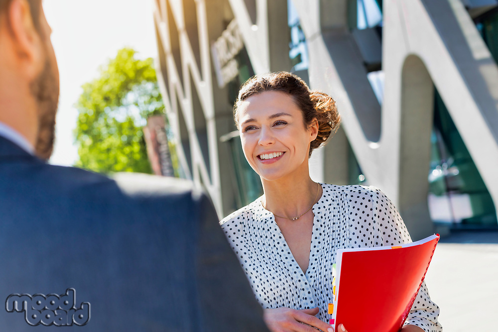 Portrait of young attractive businesswoman smiling while talking to colleague