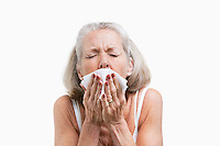 Senior woman sneezing into a tissue against white background