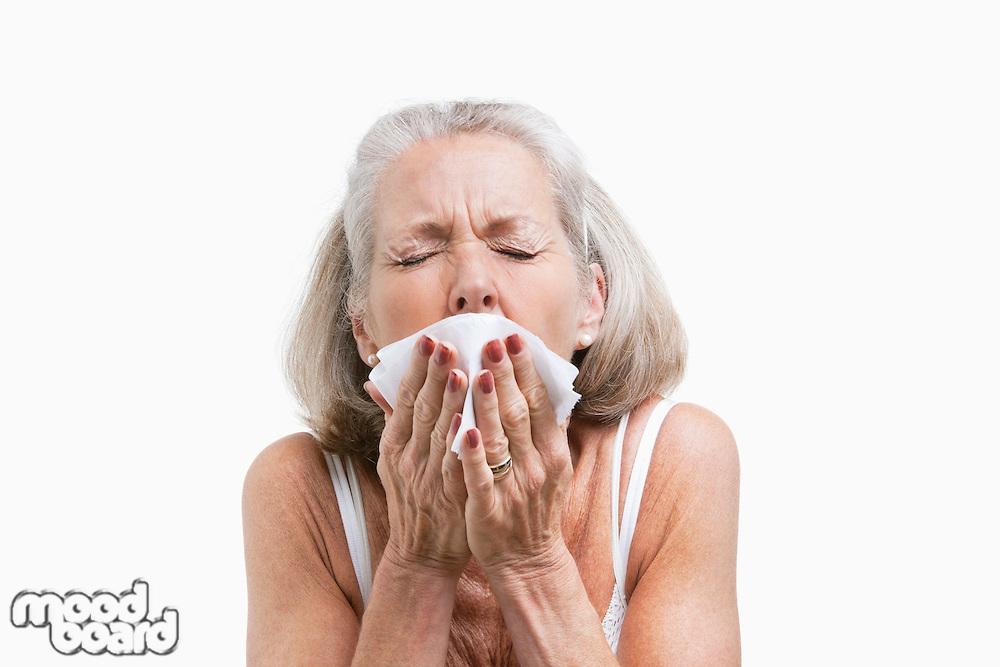 Senior woman sneezing into a tissue against white background