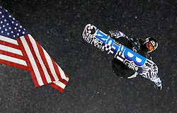 Shaun White soars past the American flag at the U.S. Snowboarding Grand Prix finals, Saturday, Jan. 23, 2010, in Park City, Utah. (AP Photo/Colin E Braley)..