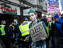 """© Licensed to London News Pictures . 09/12/2018 . London , UK . A protester carrying a """" Queers against Nazis """" placard at an anti-fascist , pro-Europe counter protest on Whitehall in Westminster as a pro-Brexit demonstration is held . Photo credit: Joel Goodman/LNP"""