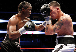 Apr 24, 2009; Newark, NJ, USA; Kassim Ouma (red/black) and Gabriel Rosado (black/white) trade punches during their 10 round junior middleweight fight at the Prudential Center.  Rosado defeated Ouma via split decision.