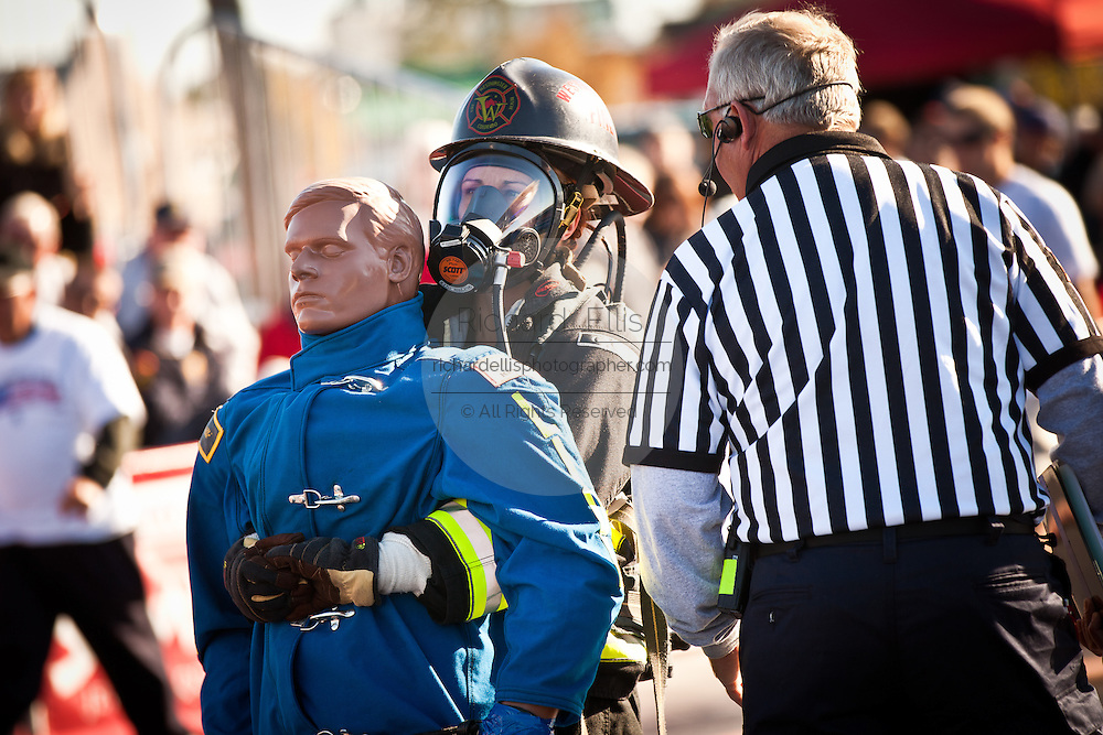 A woman firefighter is watched by the referee as she drags a 175-pound mannequin backwards during the international finals of the Firefighter Combat Challenge on November 18, 2011 in Myrtle Beach, South Carolina.