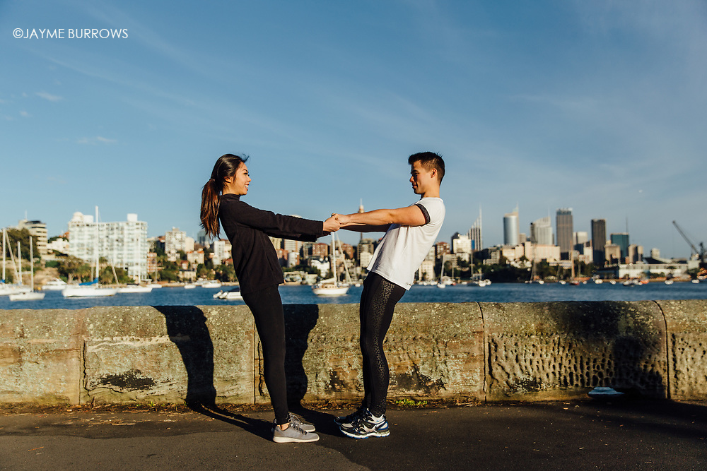 Couple stretches next to harbor in Sydney.