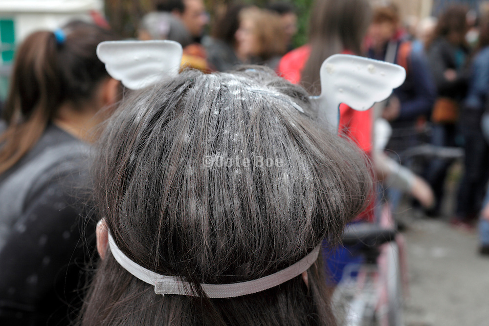 person wearing angel wing head decoration and white powder in her hair