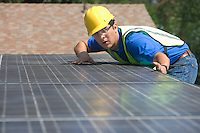 Maintenance worker measures solar array on rooftop Los Angeles California