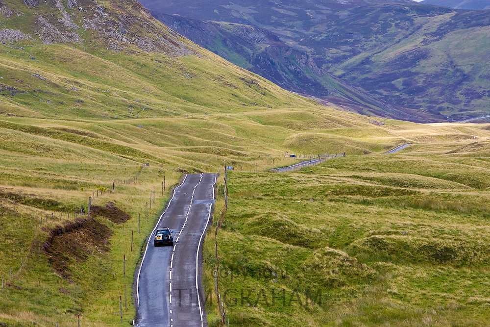 Car drives through the Glen Clunie hills and Grampian Mountains, Scotland, UK