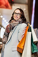 Portrait of young attractive woman walking while holding paper bags on night shopping
