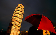 Tourist looking at the famous leaning tower of Pisa after rain.