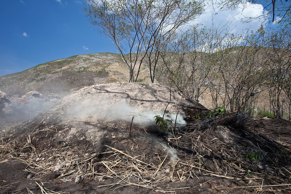 Smoke smoulders as charcoal - the primary source of fuel - is made on Ile de La Gonave in Haiti