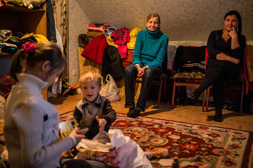 DNIPROPETROVSK, UKRAINE - OCTOBER 12: Yeva (R) and her host brother Ilya play in the attic where she, her mother, and her grandmother Svitlana Kostromina (3rd L) are living with Vira Luchnikova (R) and her family after fleeing fighting in Luhansk in Eastern Ukraine on October 12, 2014 in Dnipropetrovsk, Ukraine. The United Nations has registered more than 360,000 people who have been forced to leave their homes due to fighting in the East, though the true number is believed to be much higher.(Photo by Brendan Hoffman/Getty Images) *** Local Caption *** Svitlana Kostromina;Vira Luchnikova