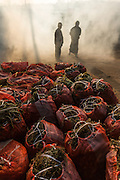 Two men in fog with bags of produce at wholesale market, Aung Ban