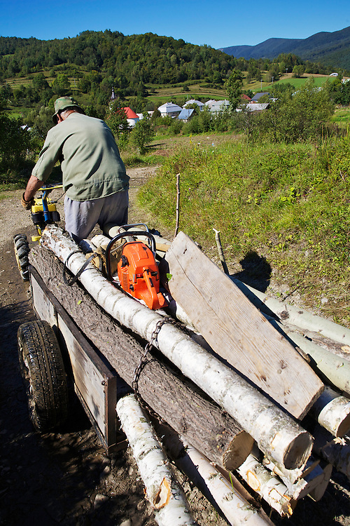 Old man bringing logs / firewood that he cut in the nearby forest home to his house in Nova Sedlica, Slovakia.
