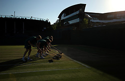 Ground staff sweep the court on day eight of the Wimbledon Championships at the All England Lawn Tennis and Croquet Club, Wimbledon. PRESS ASSOCIATION Photo. Picture date: Tuesday July 10, 2018. See PA story TENNIS Wimbledon. Photo credit should read: Steven Paston/PA Wire. RESTRICTIONS: Editorial use only. No commercial use without prior written consent of the AELTC. Still image use only - no moving images to emulate broadcast. No superimposing or removal of sponsor/ad logos. Call +44 (0)1158 447447 for further information.