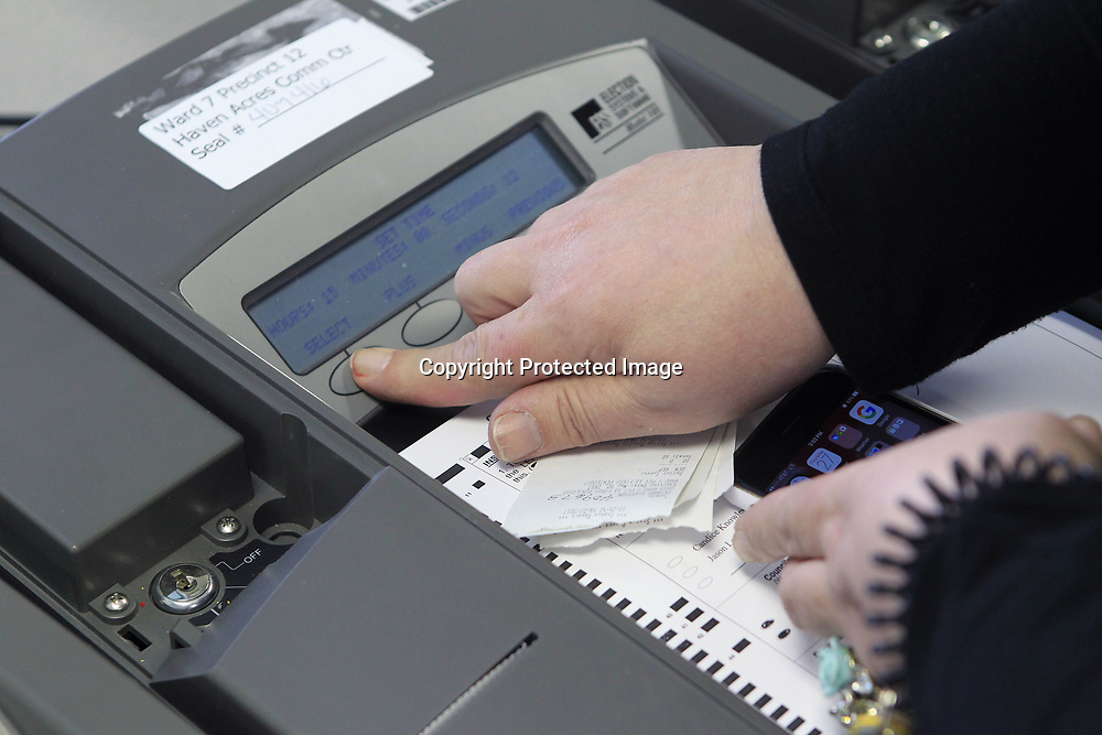 Barbara Hall, a worker with ES&S, Election Systems & Software, sets the time on a voting machine during a testing on Thursday at the Circuit Clerks Office in advance of next week's primary election in Tupelo.