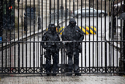 © Licensed to London News Pictures. 21/01/2018. London, UK. Police officers guard the gates at Downing Street during rainy and snowy weather. Photo credit : Tom Nicholson/LNP