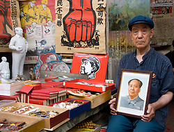 Elderly stall holder holding a portrait of Chairman Mao at antique market in Beijing China