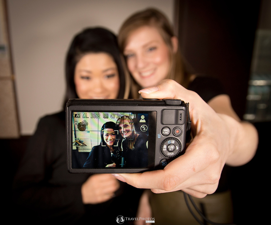 A young caucasian and a Japanese women taking selfies together at a wine bar.