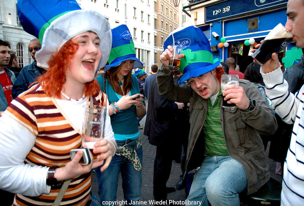 Young people dancing drinking and generally having a good time on Saint patrick's Day in London.