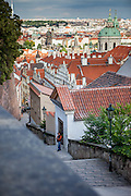A street musician is perfoming during later afternoon at the Castle Stairs (Zamecke schody) which are leading from Prague Castle down to the Lesser Town (MalaStrana).