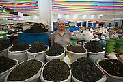 A Hui Muslim woman sells green, jasmine and oolong teas in a market in Wuzhong in Ningxia China.