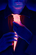 Man in suit  tightens the knot of a glowing rope tie.Black light